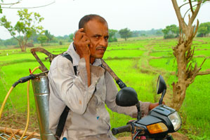 A happy farmer using mobile phones