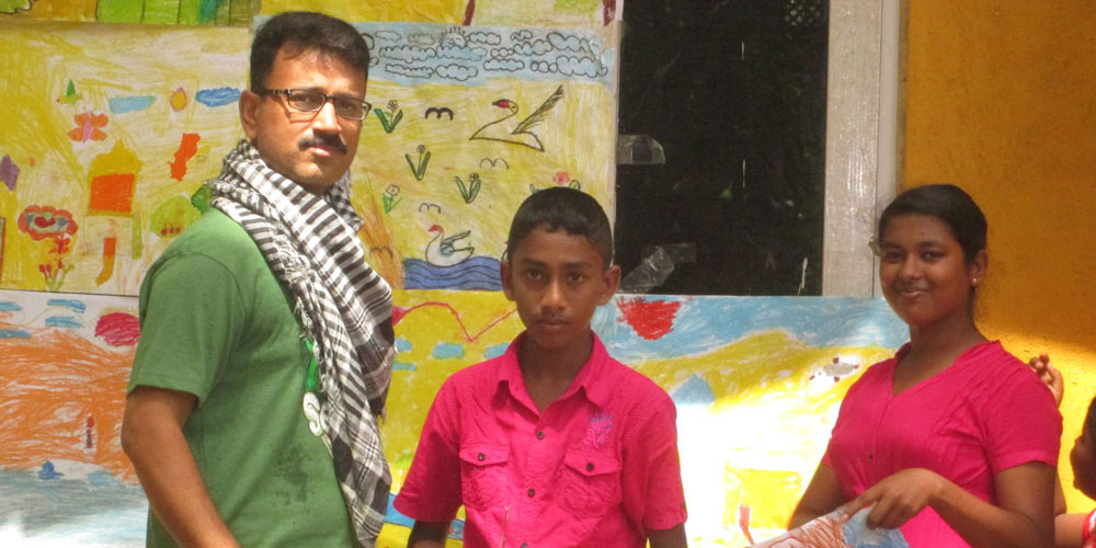 Nadeem from CPI/Eckova with children and junior students' drawings.