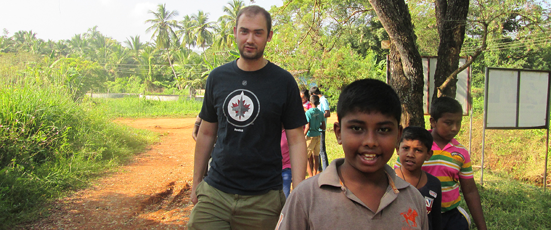 Zachary Grenzowski walking in the village with the Horizon Lanka kids