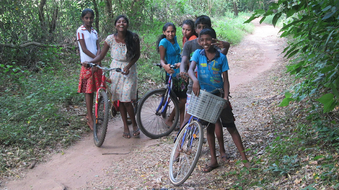 Horizon Lanka students riding bicycles in the village