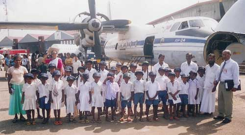 Veddah children in front of an aeroplane