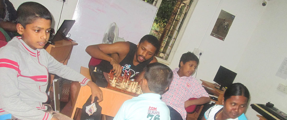 An American volunteer teaches chess to Horizon Academy students